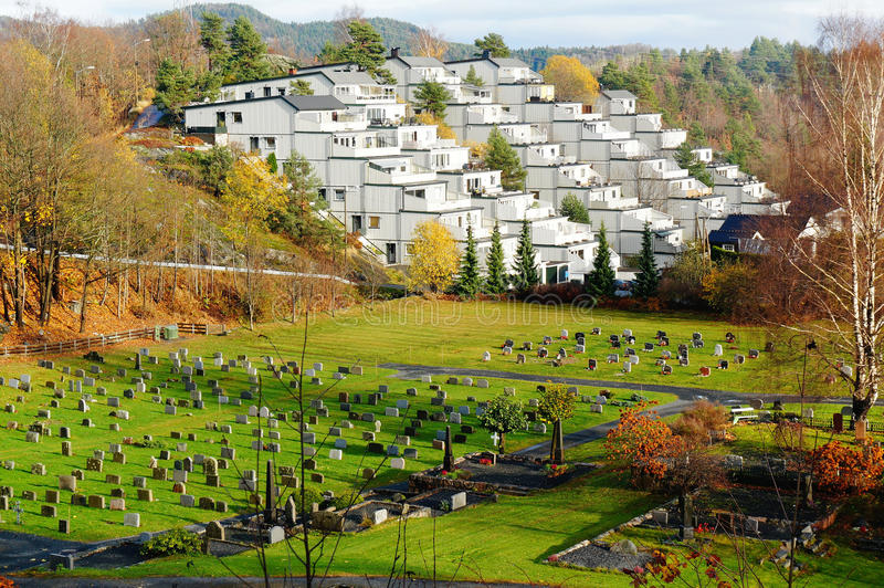 Top view of a settlement and cemetery. Top view of a settlement of white wooden houses towering over cemetery in Autumn in Norway royalty free stock photo