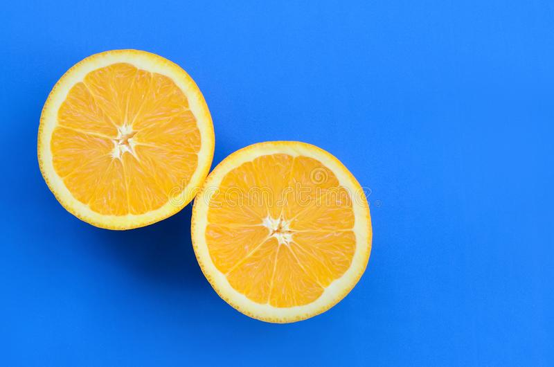 Top view of a several orange fruit slices on bright background i. N blue color. A saturated citrus texture image royalty free stock photography
