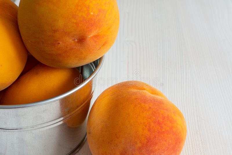 Top view of several peaches in metal bowl in closeup on white wooden background in horizonta stock image