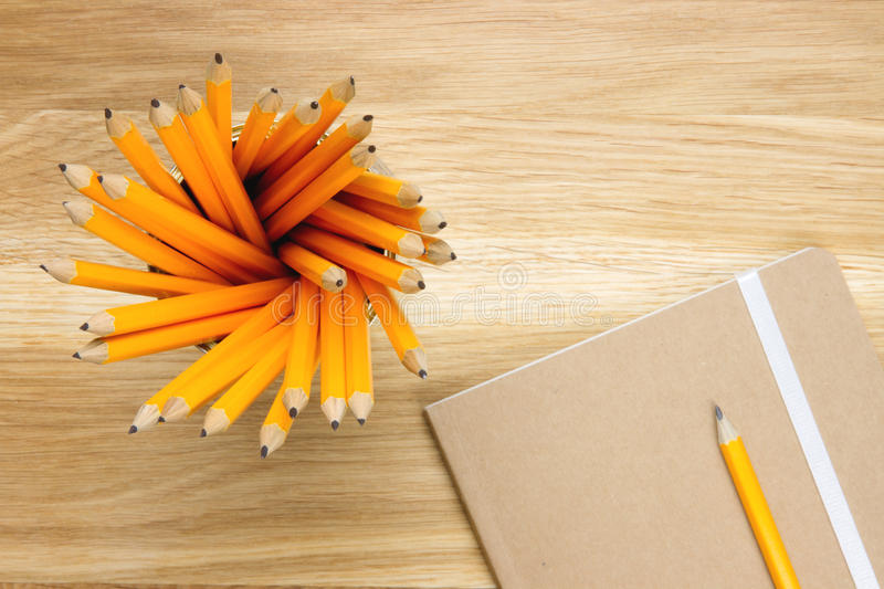 Top-view of several pencils and notebook. Top-view of several orange colored pencils and notebook on wooden desk royalty free stock image