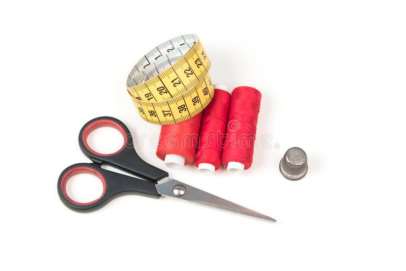 Top view of sewing accessories and tools. Red sewing threads, black scissors, yellow measuring tape and thimble on a white backgro stock images