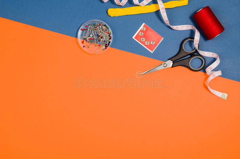 Top view of sewing or knitting accessories over blue background stock image