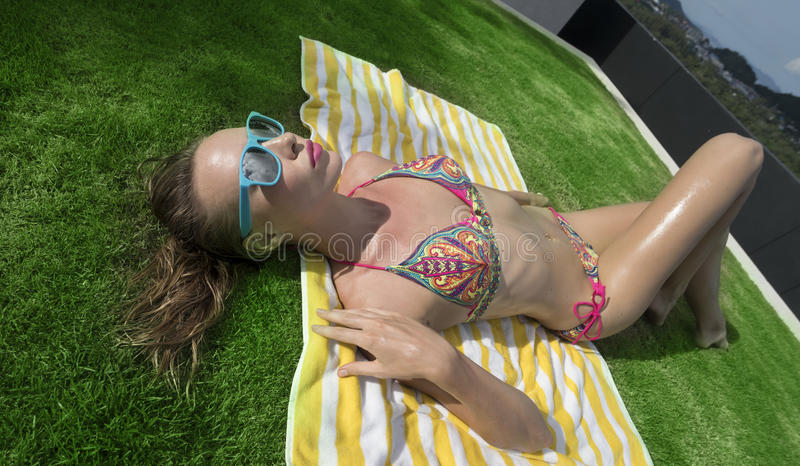 Top view of woman in bikini and blue sunglasses lying on striped beach towel over green grass background royalty free stock photography