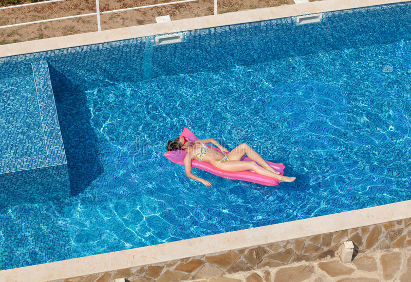 Top view of woman tanning on mattress in pool royalty free stock photography
