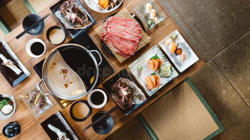 Top view of Shabu set including rare slices Wagyu A5 beef, Shabu shoyu and clear base, salmon, sushi and vegetables stock image