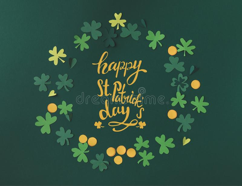 Shamrocks and coins with happy st patricks day lettering. Top view of shamrocks and coins with happy st patricks day lettering royalty free stock photo