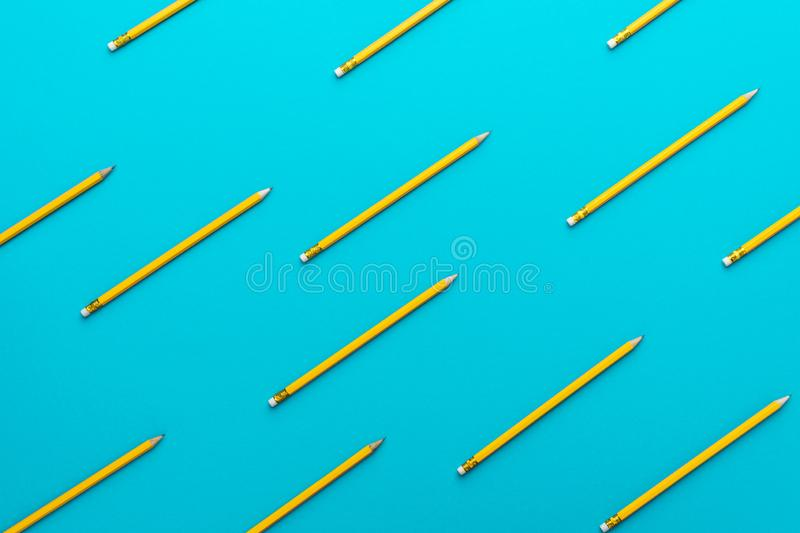 Top view of sharpened simple yellow pencils over turquoise blue background stock image