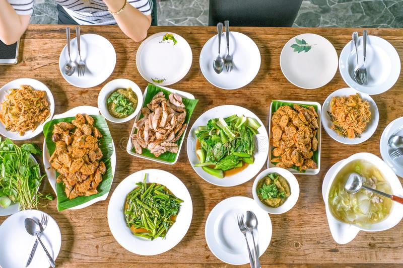 Top view shot; Thai local foods arranged on the wood table, and Asian woman was waiting and ready to eat stock photo