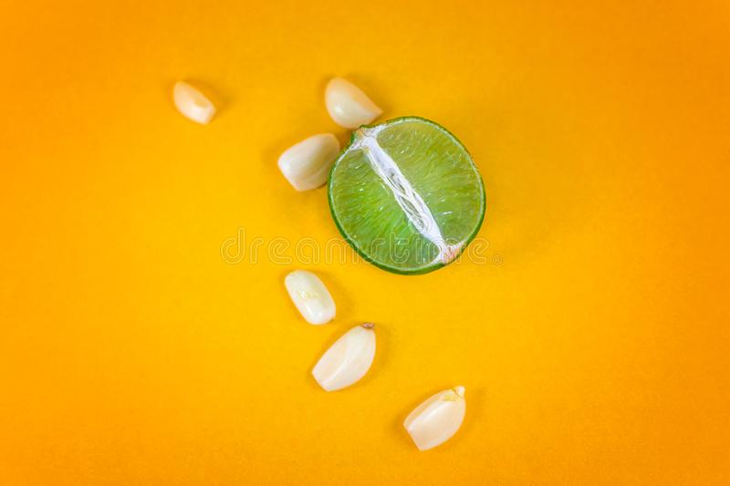 Top view of a slice of lemon surrounded by garlic cloves over a background of vibrant yellow. Natural medicine, flu and. Immunity concept. Some space for stock images