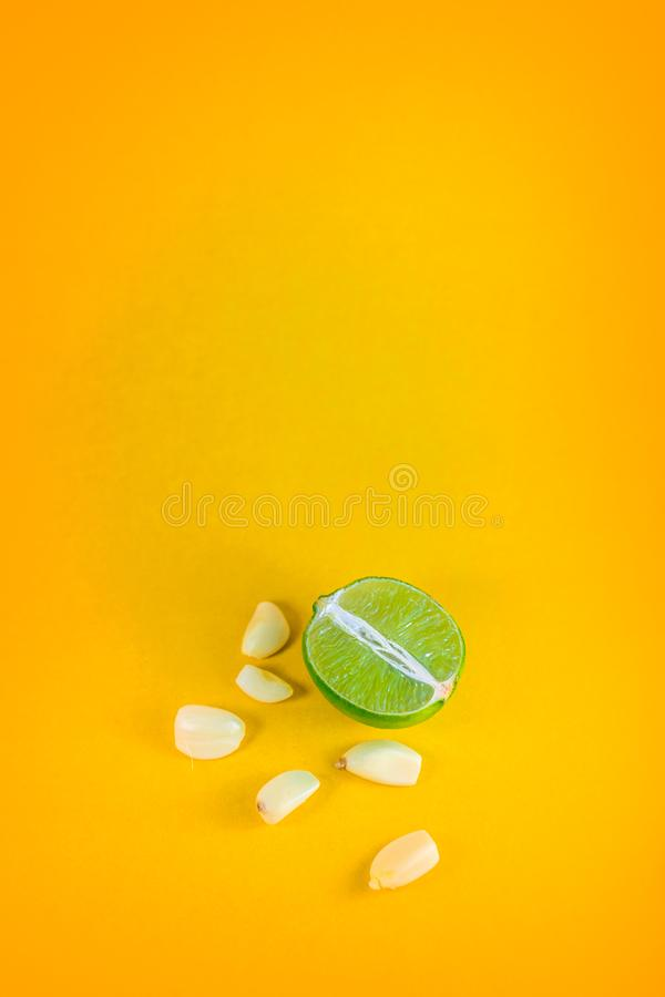 Top view of a slice of lemon surrounded by garlic cloves over a background of vibrant yellow. Natural medicine, flu and. Immunity concept. Pop art style with stock photography
