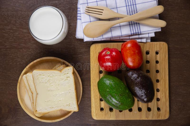 Top view sliced bread toped with condensed milk on wooden plate and fresh milk. Tomato,avocado on breakfast healthy and diet food concept stock photography