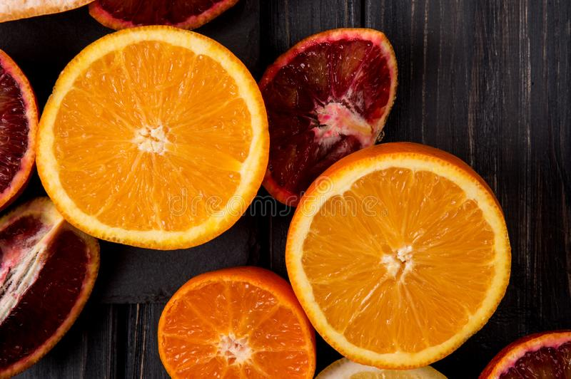 Top view. Sliced in half juicy oranges on a dark wooden background royalty free stock photos