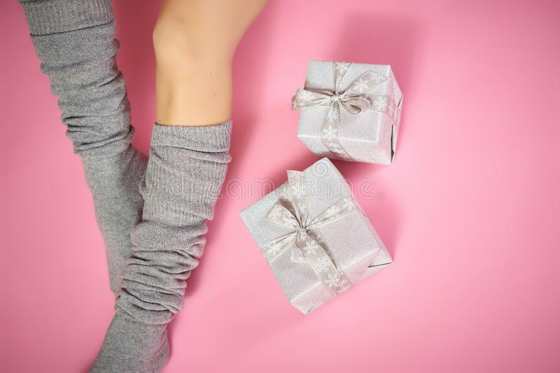 Top view of slim female legs in warm gray socks with xmas gifts on a pink background. Top view of slim female legs in warm gray socks with xmas gifts on a light royalty free stock photo