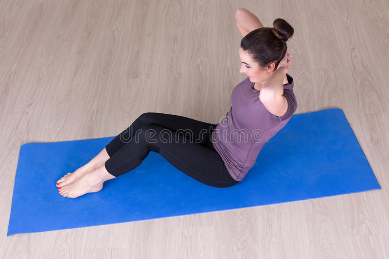 Top view of slim woman doing sport exercises on the floor. Top view of young slim woman doing sport exercises on the floor royalty free stock photo