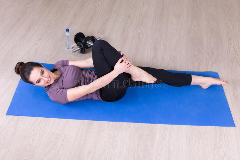 Top view of slim woman doing stretching exercises on the floor. Top view of young slim woman doing stretching exercises on the floor royalty free stock photo