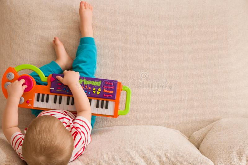 Top view on small cute toddler boy sitting on the sofa and playing on the toy piano. A little boy learning to play piano stock images