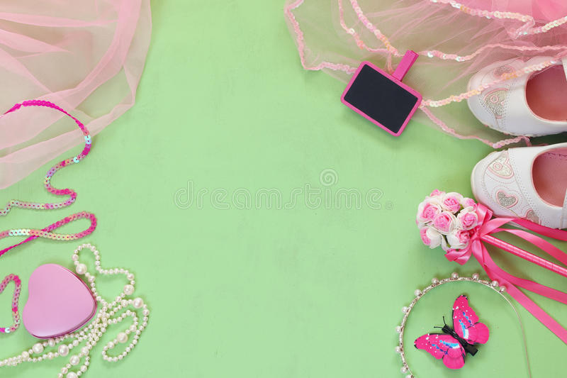 Top view of Small girls party outfit: white shoes, crown and wand flowers next to small chalkboard. bridesmaid or fairy costume.  stock photos