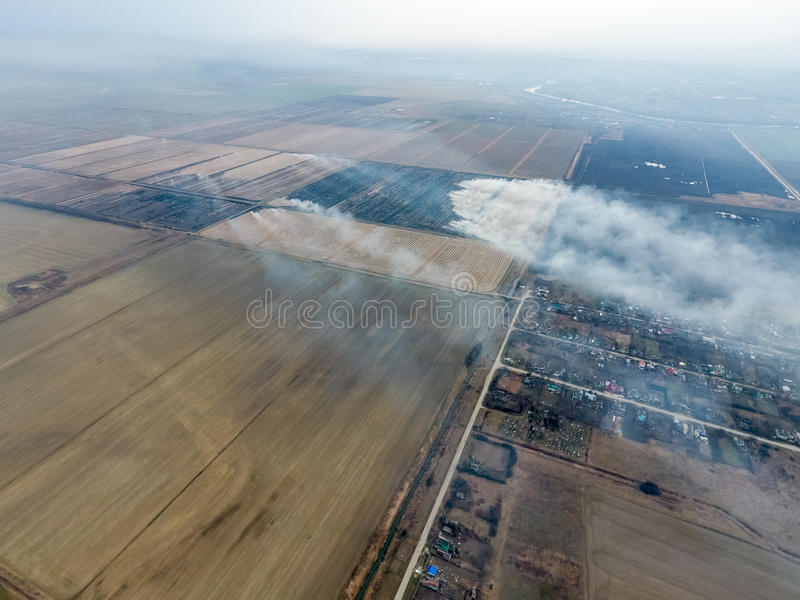 Top view of the small village. Smoke from the burning of straw i royalty free stock image