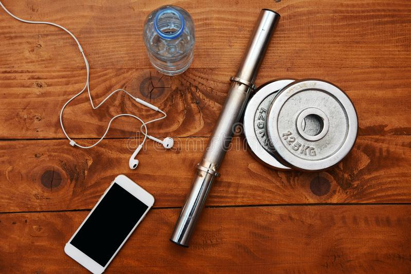 Top view of smartphone, earphones, bottle of water and weights on wooden background. Close up view. Top view of smart phone, earphones, bottle of water and stock photography