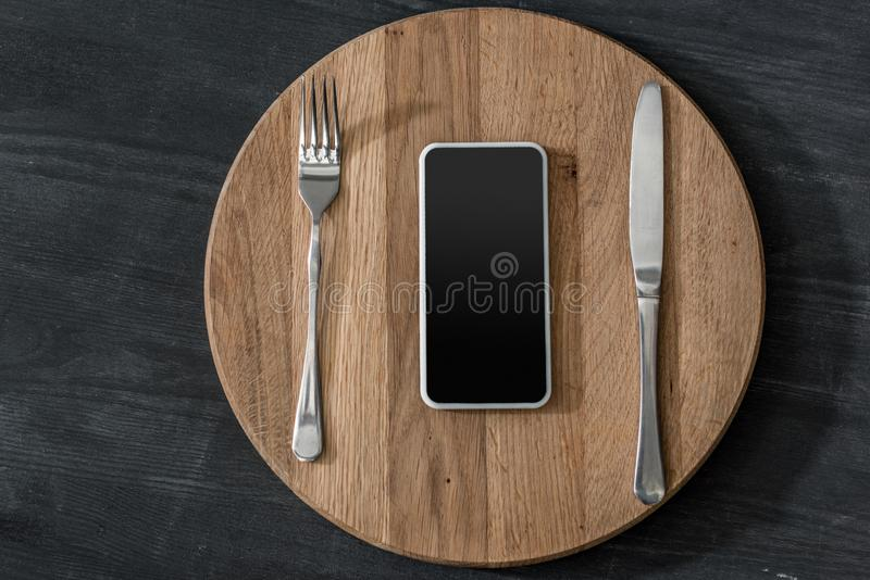 top view of smartphone lying on wooden board with cutlery, phone addiction concept royalty free stock images