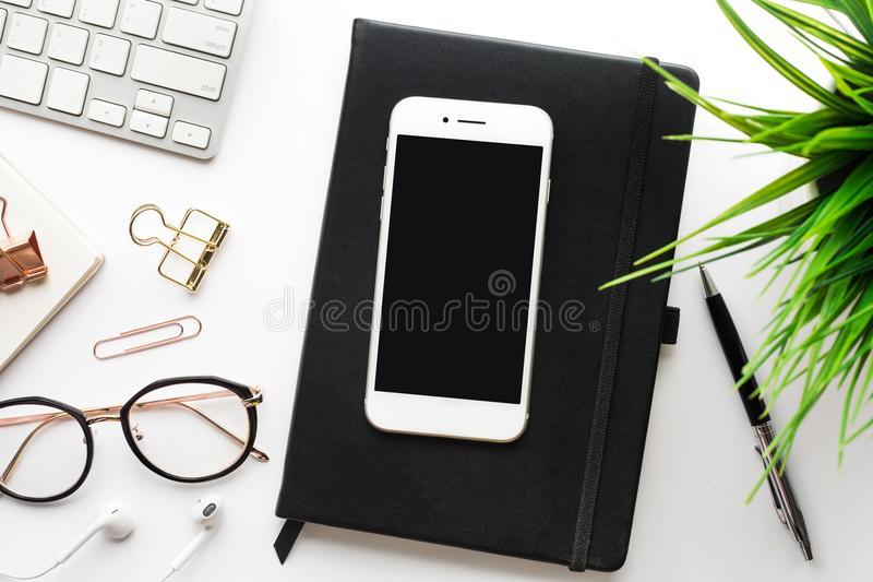Top view of smartphone on office desk table with modern accessories royalty free stock photography