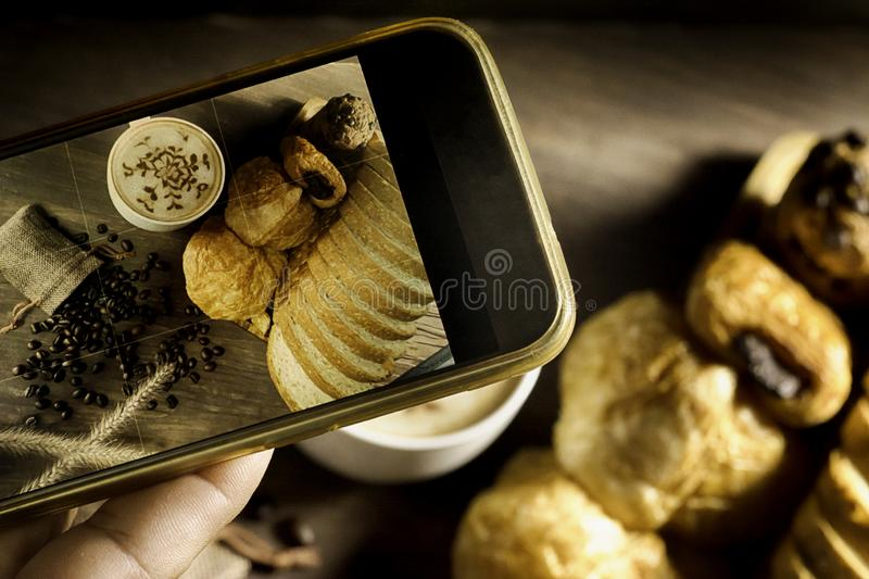 Top View-smartphone taking photo homemade bread stack placed on table in kitchen with morning sunlight consists of bread slices,. French bread,muffins and stock images