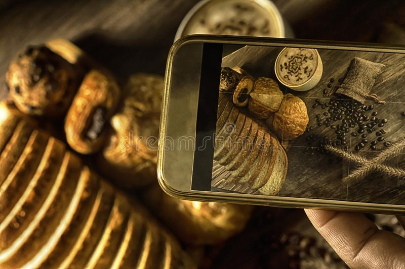 Top View-smartphone taking photo homemade bread stack placed on table in kitchen with morning sunlight consists of bread slices,. French bread,muffins and royalty free stock image