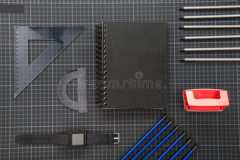 Top view of smartwatch and organized office supplies. On black stock photo