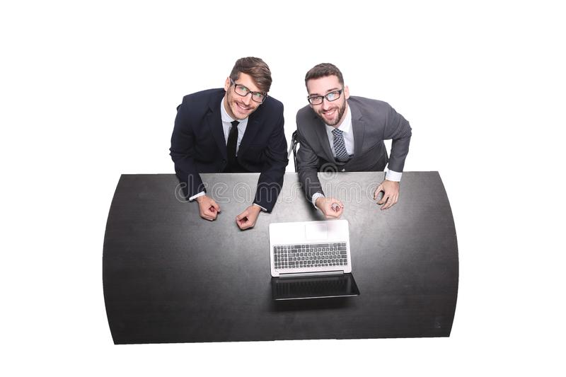 Top view. smiling business colleagues sitting in front of an open laptop stock image