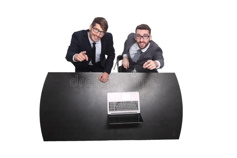 Top view. smiling business colleagues sitting in front of an open laptop royalty free stock image