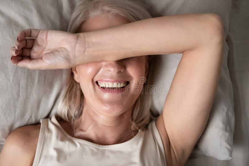 Top view of smiling elderly woman awaken in comfortable bed stock photo