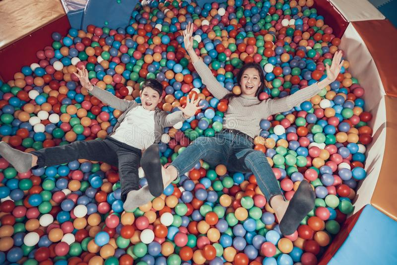 Top view. Smiling mom and son in pool with balls royalty free stock image