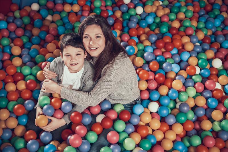 Top view. Smiling mom and son in pool with balls royalty free stock photo