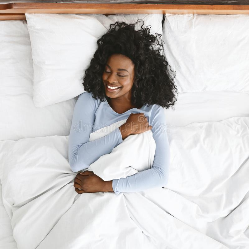Top view of smiling woman waking up in her bed. Young well-slept african woman waking up in bed, smiling and holding blanket with closed eyes, empty space, top royalty free stock image