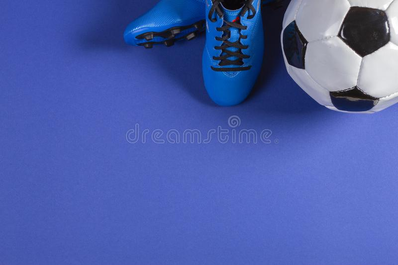 Top view of soccer ball and pair of soccer football sports shoes on blue background stock images