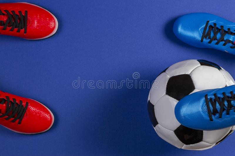 Top view of soccer ball and two pairs of soccer football sports shoes on blue background.  stock photo