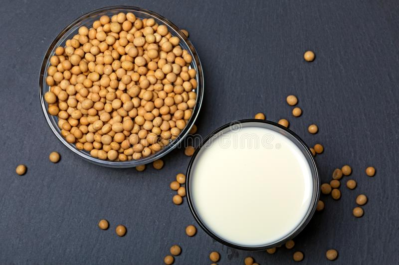 Top view of soy seeds and glass of milk on slate background royalty free stock photography