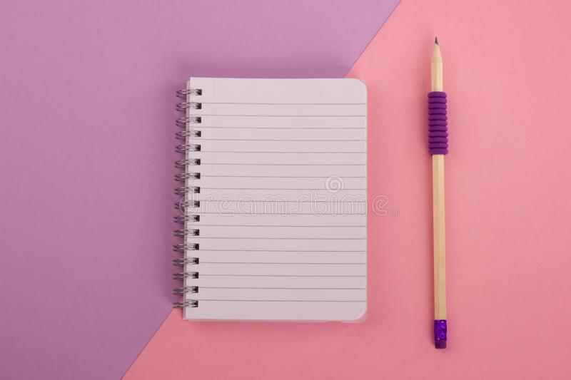 Spiral notepad and pencil on pastel background. royalty free stock image