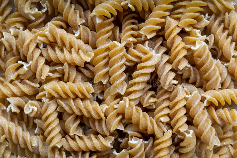 Top view of spiralli whole grain pasta pattern. Flat lay raw spilled Italian pasta view from above royalty free stock image