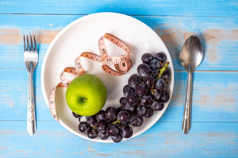 Top view spoon and fork, green apple and black grapes in white dish with pink Measuring tape on blue wood table background. stock photos