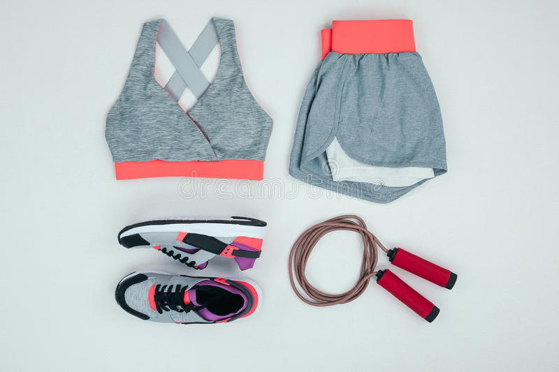 Sportswear with sneakers and skipping rope isolated on grey stock photos