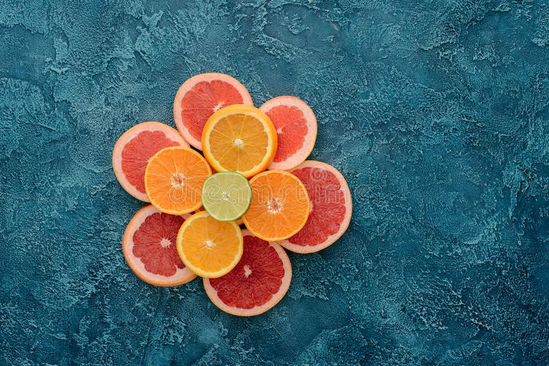 top view of stacked various citrus fruits slices on blue royalty free stock photos