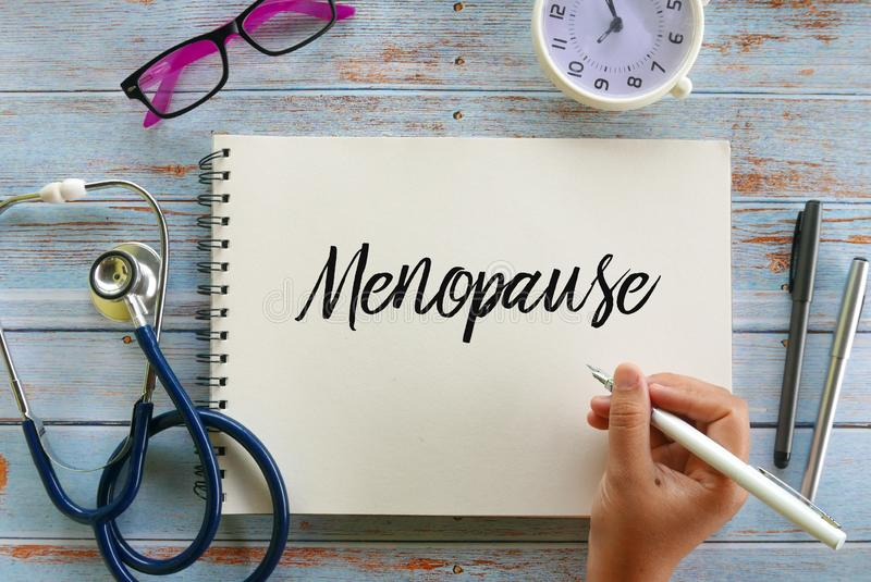 Top view of stethoscope,glasses,clock,pen and hand writing & x27; Menopause & x27; on notebook on wooden background royalty free stock photos
