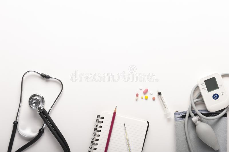 Top view of stethoscopes, Automatic portable blood pressure or heart rate monitor and drugs on white background stock images