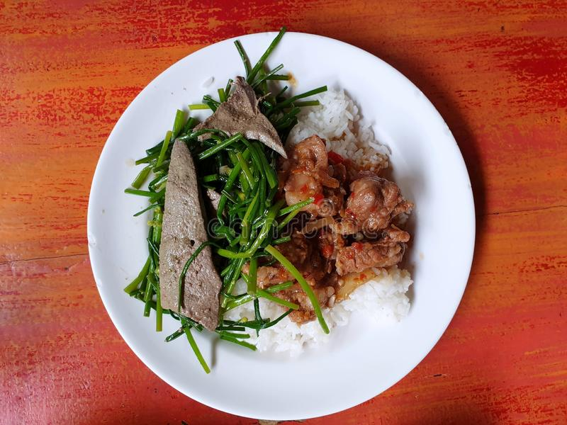 Top view of stir fried pork liver with chinese chives and fried pork with shrimp paste on jasmine rice stock photography