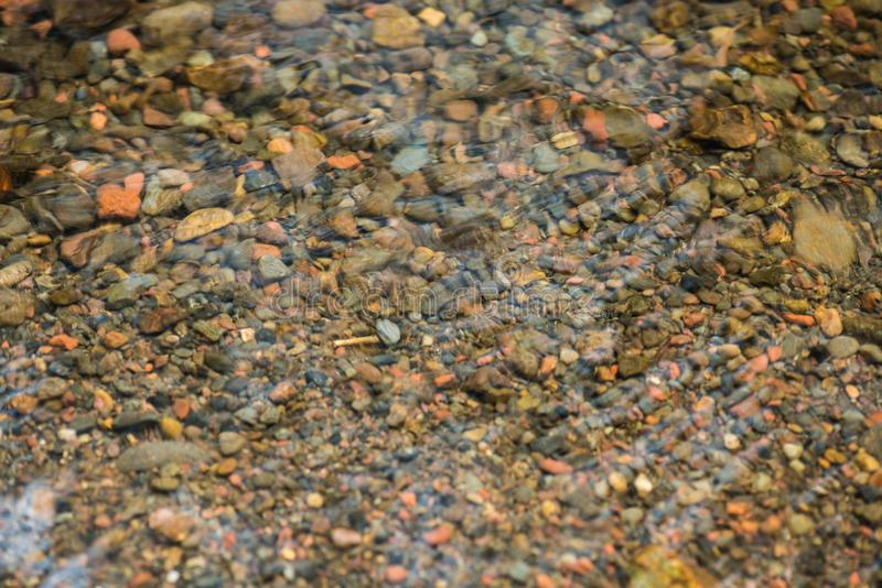 Top view stones in the river. The Rock ground cover water backgrounds. Small pebble stones in creeks stock images