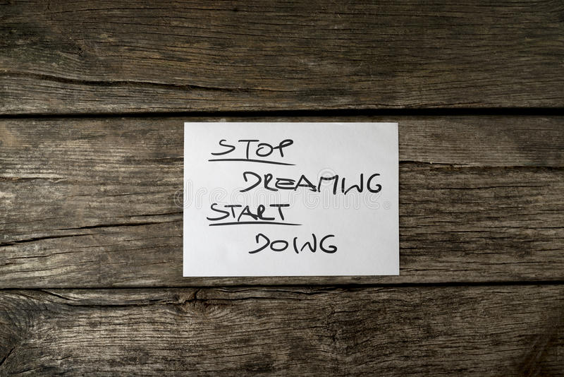 Top view of a Stop dreaming start doing message. Written on a white card lying on wooden rustic desk stock image