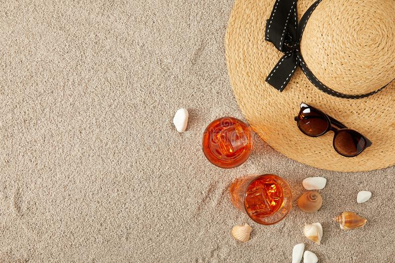 top view of straw hat, cocktails, seashells and sunglasses on sand stock photography