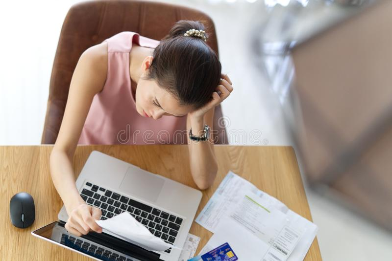 Top view of stressed young sitting Asian woman worry about her credit. royalty free stock photos