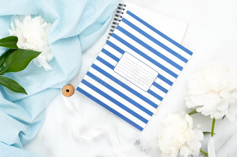 Top view striped notebook, white peony flowers and feminine accessories on marble background. Minimalistic flat lay composition,. Beauty or fashion blog banner royalty free stock photo